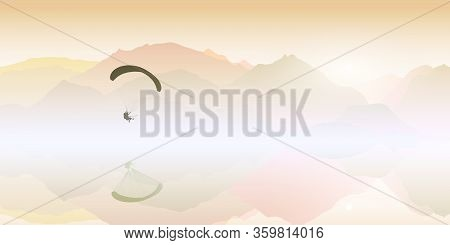 Silhouette Of Flying Paraglider Take A Selfie With Action Camera Above The Mountain Lake At Sunrise.