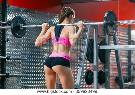 Back View Of Muscular Girl With Sexy Buttocks Performing Squat Exercises With A Barbell In Modern Gy
