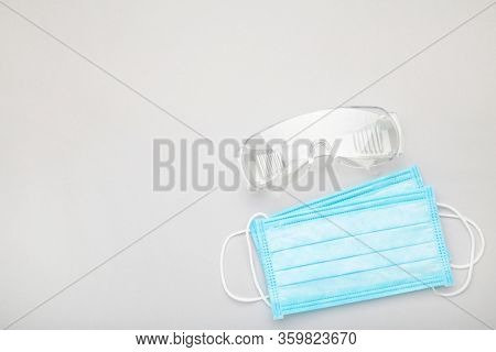 Glasses And Medical Disposable Mask For Protection Against Viruses On A Grey Background. Covid-19