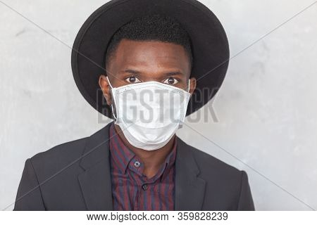Young African Black Man In A Suit And Hat Against A Gray Concrete Wall Is Afraid Of A Coronavirus Ep