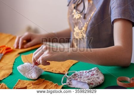 A Young Girl Seamstress Takes A Needle From A Pillow For Needles. Orange Cloth On A Green Table. Foc