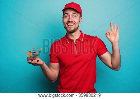 Confident Worker With Red Uniform Guarantees On Online Shopping. Cyan Background