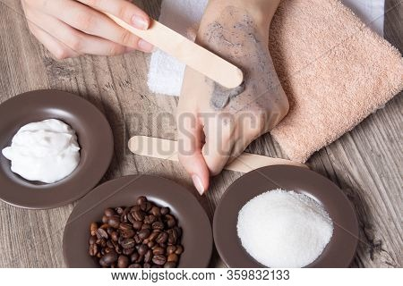 A Woman Puts A Spatula Of Coffee Homemade Scrub On Her Hand. Spa, Beauty. Ingredients For Making Scr
