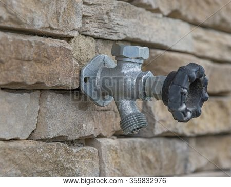 Horizontal Close-up Shot Of An Outdoor Water Faucet Attached To A Stone Wall. The Background Is Part
