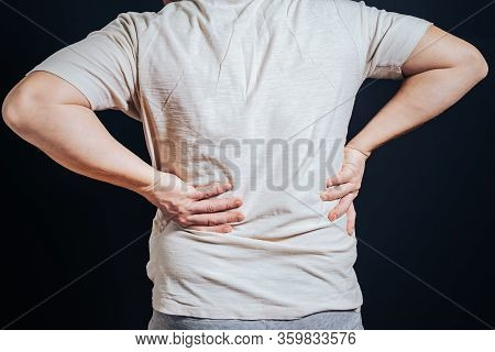 The Guy Put His Hand On His Sore Back, Standing Against The Black Background. The Concept Of Trauma,