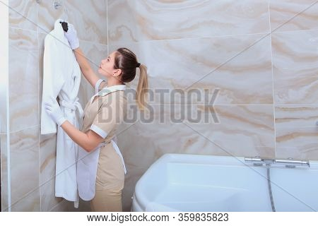 The Maid In The Bathroom Hangs A White Terry-cloth Robe On A Hanger. The Concept Of Service To Our G