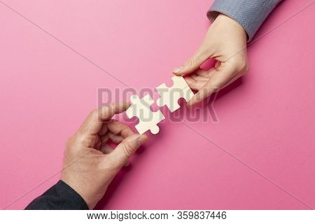 Two Hands Connect Puzzles On A Pink Background. Cooperation And Teamwork In Business. Collaboration