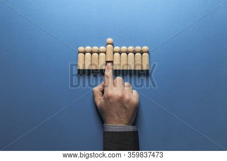 Hand Of Businessman Chooses Best Candidate Among Figures Of Hired People. Recruiter And Headhunter C