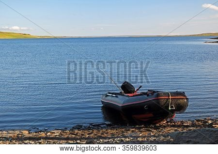 Rigid Inflatable Boat With A Fishing Rod On The Lake Shore On The Background Of The Lake