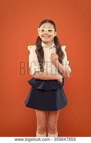What Does It Mean Being Smart. Little Smart Schoolgirl On Orange Background. Child Smart Look Throug