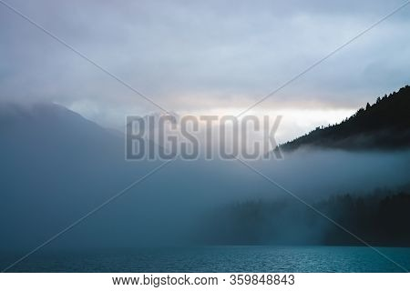 Beautiful Mountain Lake Among Huge Mountains And Forest In Mist In Golden Hour. Sun Shines Through D