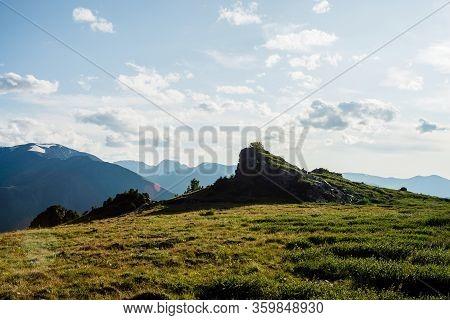 Wonderful Alpine Landscape With Beautiful Rock On Green Mountain Peak In Sunlight. Solar Flare On Hi
