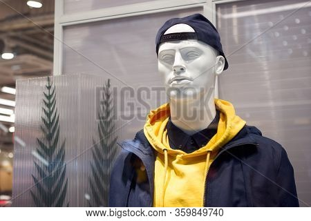 Male Mannequin In A Baseball Cap, Shirt And Hoodie On A Shop Window
