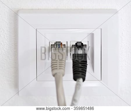 Two Data Patch Cords Plugged Into A Wall Data Internet Rj45 Socket.