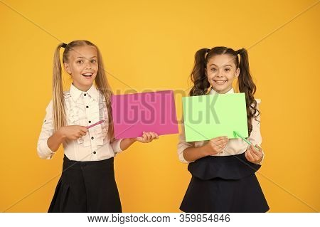 Important Lesson You Should Learn. Cute Small Children Reciting Lesson With Pen And Paper On Yellow