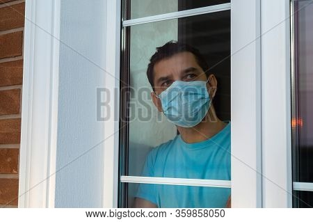 Isolation At Home For Self Quarantine. Young Man In Medical Mask Is Looking Out Window. Guy Stay Hom