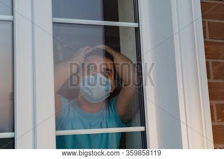 Man In A Medical Mask Near Window. Man Tired Of Quarantine Of Coronavirus. Sick Sad Man In Medical P