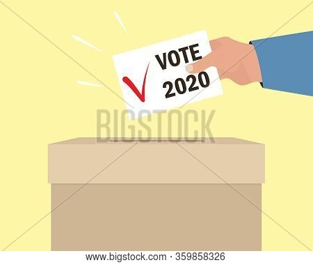 Voting Concept. Human Hand Puts An Envelope In Ballot Box. Text Vote 2020 And Checkmark On Paper. Fl
