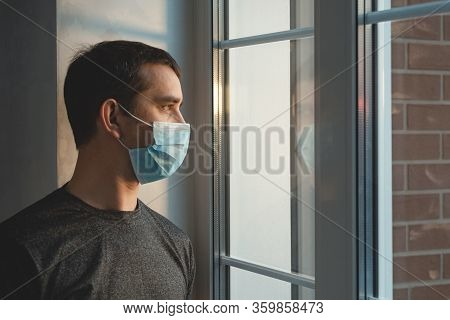 Quarantine Self-isolation. Sad Young Man In A Medical Mask Who Looks Out The Window Through The Wind