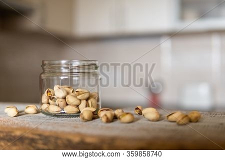 Pistachios In A Jar And Scattered Pistachios Around A Jar Which Standing On A White Vintage Table Wi