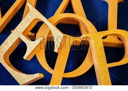 Letters Cut Out Of Polystyrene With Gold Color On A Blue Background. Blank For Decoration, Logo Maki