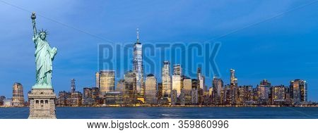 Panorama statue of liberty Landmark of New York with aerial view of New York city Lower Manhattan skyscraper skyline building cityscape at dusk from New Jersey in background.
