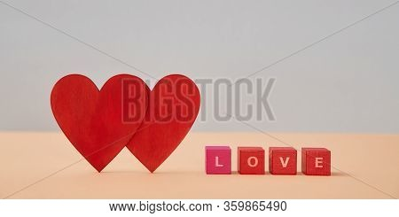 Amour And Fondness. Saint Valentines Day. Love And Relationship. Two Red Hearts, Wooden Cubes With L