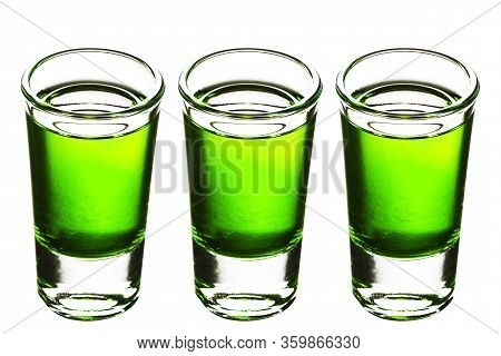 Three Vodka Shots Isolated On White. Vodka Glass In A Row. Green Booze Liquor. Weekend Party Symbol