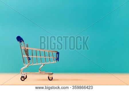 Empty Shop Cart Miniature Symbol. Small Metal Trolley. Shopping And Purchasing Goods. Retail And Who