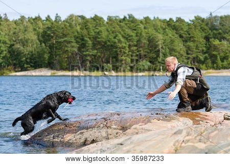 The Labrador retriever fetch a dummy for its owner poster