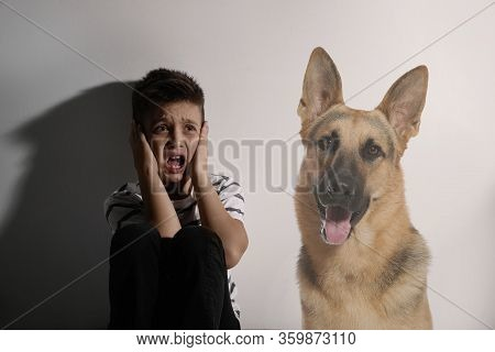 Scared Little Boy Suffering From Cynophobia On White Background. Irrational Fear Of Dogs