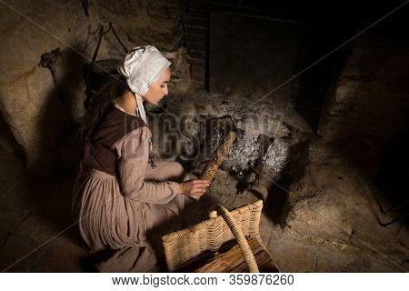 Renaissance portrait in Rembrandt style of a young woman in medieval peasant costume working near the authentic fireplace of a property released French castle