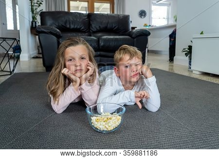Covid-19 Outbrek. Bored Brother And Sister In Isolation Watching Tv During Coronavirus Lockdown