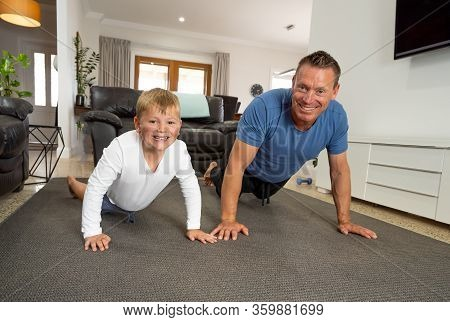 Covid-19 Shutdown. Father And Son Having Fun Exercising Together And Staying Physically Active At Ho