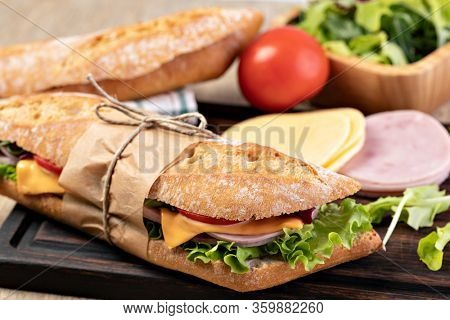 fresh submarine sandwich with ham, cheese, bacon, tomatoes, lettuce, on wooden cutting board