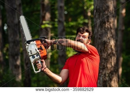 Lumberjack Concept. Lumberjack With Chainsaw In His Hands. Logging. Illegal Logging Continues Today.