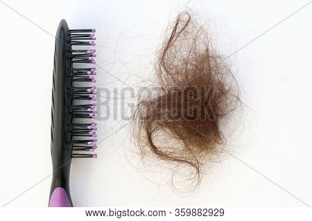 Black Comb And A Bundle Of Brown Hair On A White Background. Comb And Fallen Combed Hair Top View. T