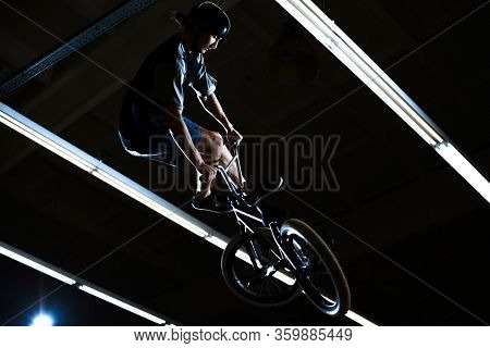 BMX Rider Doing Extreme Tricks on the Bike in the Dark Skatepark Indoor. Healthy and Active Lifestyle.