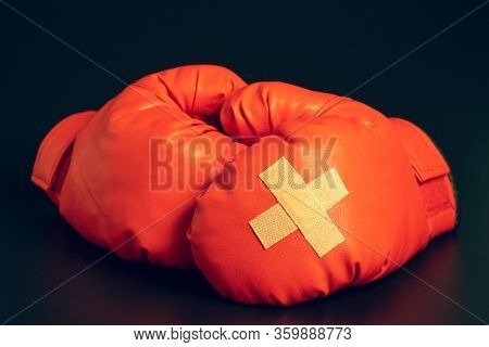 Red Boxing Gloves In The Dark Background. Adhesive Plaster Across Each Other On Boxing Gloves. The I
