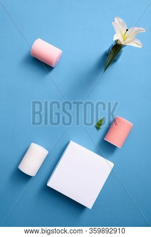 Minimal mock up of white beauty box with wax candles and flower over blue. Top view.