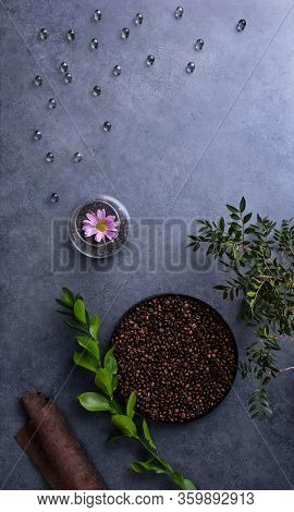 Top view of abstract spa background - flower, glass drops, coffee beans and fresh leaves over concrete desktop