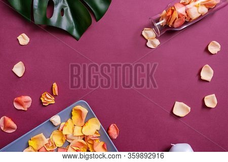 Rose petals on a plate and in a glass jar on color background. Top view with copy space at the center.