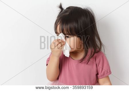 Little Asian Girl Holding A Tissue And Blow Her Nose. Kid With Cold Rhinitis. Virus And Infection. C