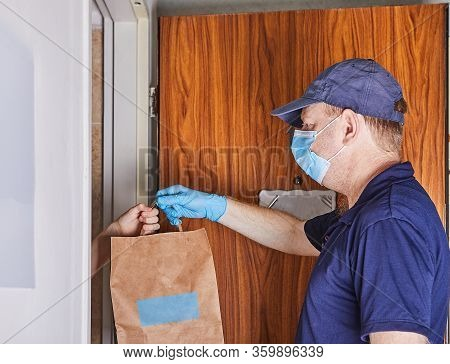 Delivery Man Holding Paper Bags In Medical Rubber Gloves And A Mask. Quarantine. Coronavirus. Copy S