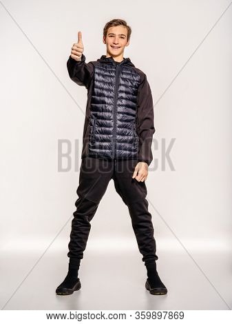 Young man in a black clothing shows big thumbs up. Trendy guy in a black clothes. Teenager dressed in a stylish clothing, poses in a studio on a white background. White boy is showing big thumb.