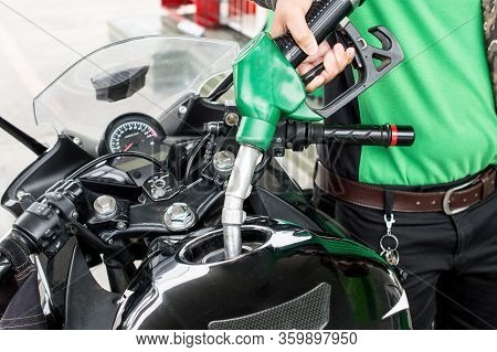 Close-up Of Person Hand Refilling Gas To The Motorcycle Barrel Tank In Gas Petrol Station.