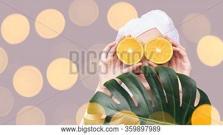 Girl Hold Orange Slice. Citrus Fruit Hidding Face. Antioxidant Home Care Routine. Facial Energy Prod
