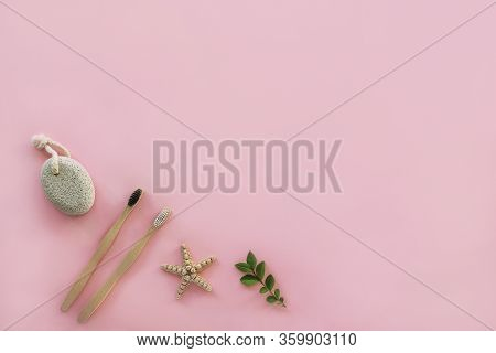 Flat Lay Accessories For Hygiene And Body Care: Pumice Stone, Wooden Toothbrushes On Pink Background