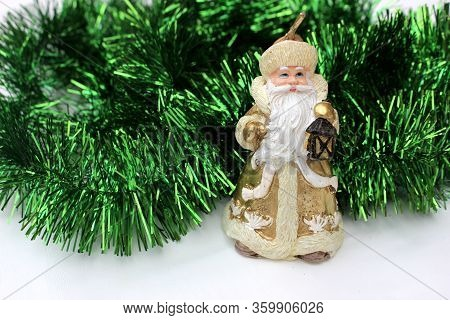Statuette Of Santa Claus On A Green Background. Golden Santa Claus Candle Isolated On White. Saint N