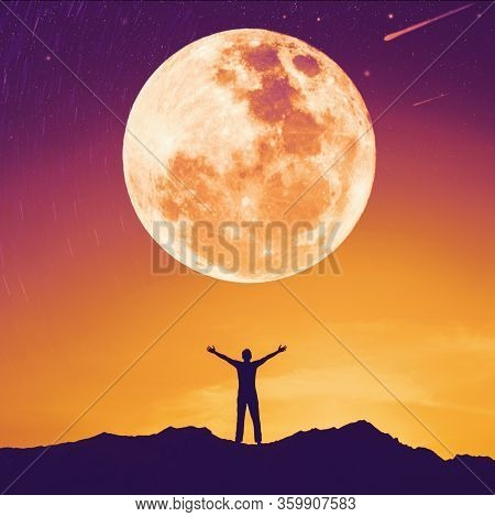 Man Raise Hand Up On Top Of Mountain With Sunset Sky And Full Moon Star Abstract Background. Copy Sp